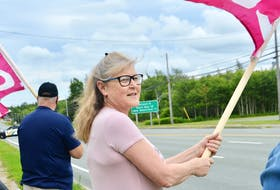 As a police vehicle drives into the parking lot of police headquarters on Grand Lake Road, picketers, including Special Const. Sharon MacLeod, were in front on Friday protesting the CBRM's decision to not reclassify special constables so they're paid equally with their counterparts across the province. ELIZABETH PATTERSON/CAPE BRETON POST