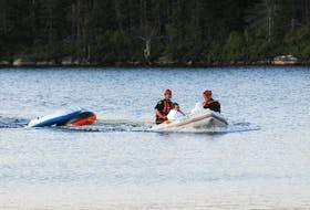 SJRFD water rescue team members Lieut. Rob Keats, left, and Capt. Craig Cox, right, head back to shore on Gull Pond on the Foxtrap Access Road Thursday night after they rescue two individuals stranded there after one of their rubber dingy's capsized. -Joe Gibbons/The Telegram
