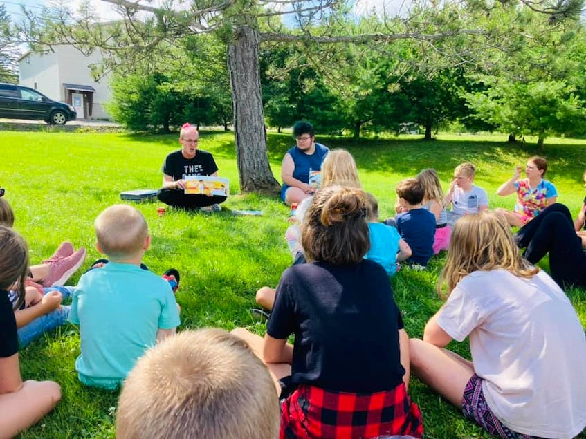 Cape Breton Youth Project educators Mitch Hill, left, and Sefin Stefura read to the campers. CONTRIBUTED