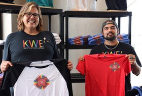 Shayne Stanger, left, and Trenton Smith hold up Mi'kmaq Printing and Design's new Pride-themed shirts designed by Misiksk Jadis.