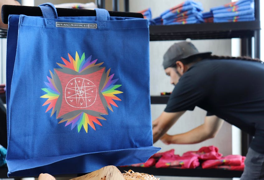 Trenton Smith of Mi'kmaq Printing and Design organizes the company's new Pride-themed shirts. The tote bag shares the same design as the shirts, a traditional Mi'kmaq eight-point star with Pride colours added. - Logan MacLean • The Guardian