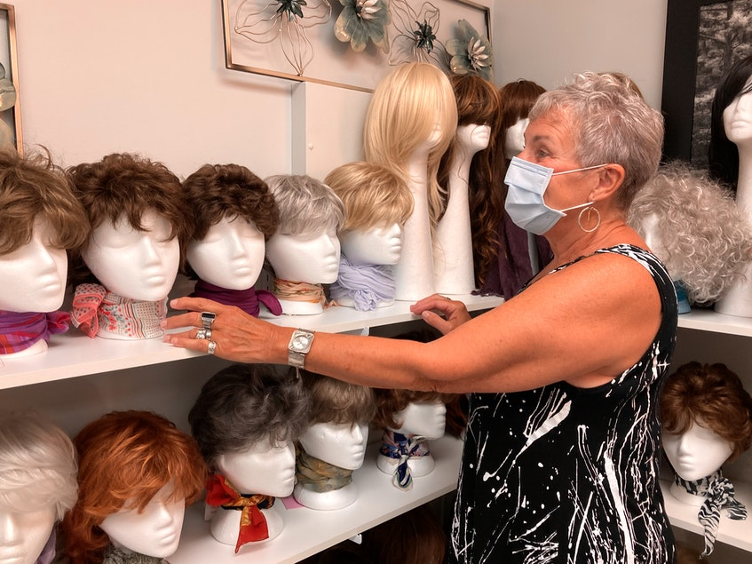 Clare Bishop, board member with the Northside-Harbourview Hospital Foundation, adjusts some of the wigs on display at Northside General Hospital's wig bank. Lynn Gilbert/Nova Scotia Health - Contributed