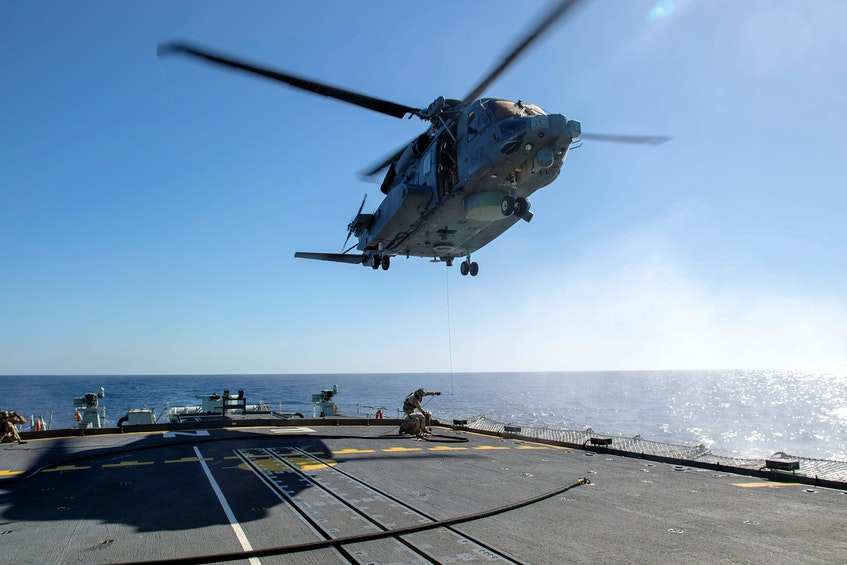 Air detachment members aboard HMCS Fredericton attach a fueling hose on the hoist cable of a CH-148 Cyclone helicopter during Operation Reassurance at sea Feb.15, 2020, in this picture obtained from social media. Picture taken February 15, 2020. - Cpl. Simon Arcand / Canadian Armed Forces via Reuters