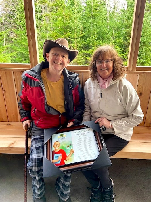 Ken LeBlanc sits with the love of his life, wife Marguerite, at his outdoor retirement party on Nov. 6, 2020. They are holding a framed replica of the sign that is next to the wishing well on Riverside School's Knowledge Path which was created and dedicated to Ken, the former after school coordinator who took students on adventures through the woods where the Knowledge Path now is. CONTRIBUTED