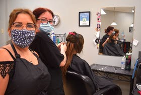 Tracy Wood, left, and Jessica Elliott, hairstylists at Scissor Haven Salon and Barber Shop, are happy to once again be greeting clients such as Angelina Gouchie who believes the hair industry should be considered an essential service because of the mental health benefits it offers. Harry Sullivan