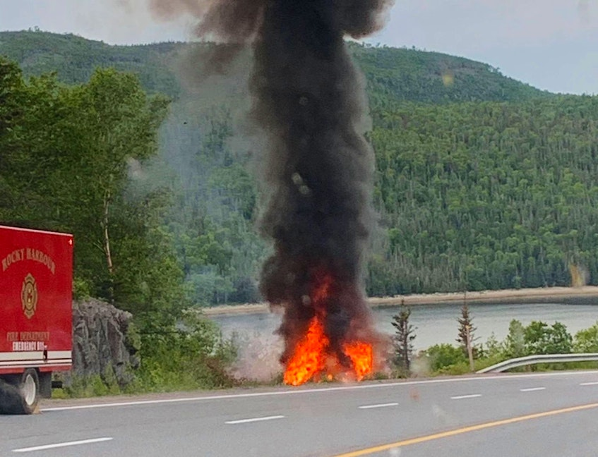 The vehicle involved in an accident on Route 430 near the entrance to Gros Morne Mountain on July 8, 2020 was fully engulfed in flames in this picture taken shortly after passersby helped free a woman who was trapped inside. - Contributed