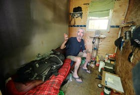 Inside Allan DeYoung's temporary shelter is a cot with a sleeping bag on top, a shelf and a camping stove he uses to cook with, among other small items.