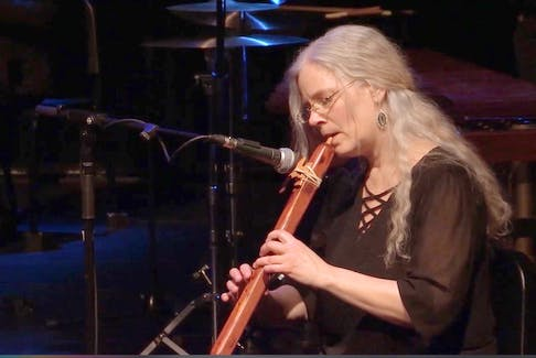 Joanne Hatfield playing a Native American Flute with the Thundermakers.