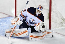 Edmonton Oilers goalie Mikko Koskinen (19) stops a shot from the Calgary Flames during the second period at Scotiabank Saddledome on Feb. 6, 2021.