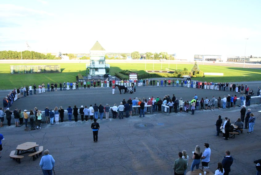 Industry members gather for a memorial horseshoe in honour of the late Vincent Poulton following Race 6 of the harness racing program at Red Shores Racetrack and Casino at the Charlottetown Driving Park on July 31. Gail MacDonald Photo