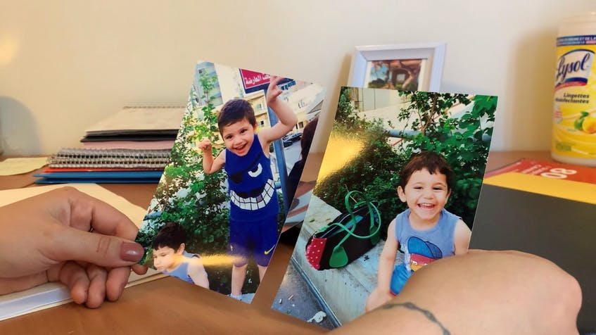 Victoria Joumaa holds old photos of her cousins Charbel and Anthony at her home in Clayton Park. Efforts to bring them and their sister Teresa to Canada have been unsuccessful so far. - Nebal Snan