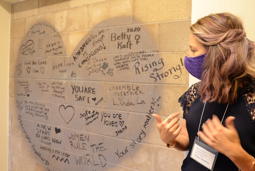 Chrysalis House executive director Ginger McPhee looks at the messages of hope and inspiration that staff members wrote on the outside of an elevator shaft in the new shelter to greet clients who arrive there. KIRK STARRATT