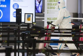A passenger covered head to toe at the International Arrivals area at Terminal 3 at Toronto Pearson International Airport on Tuesday, January 26, 2021.