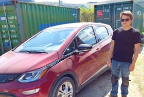 Phil Rideout bought the first electric car to make its way to the north coast of Labrador for his stepson, Trevor, pictured with the Chevrolet Bolt. In the background is a container they modified with solar panels, an inverter and batteries to charge the car using sunlight.