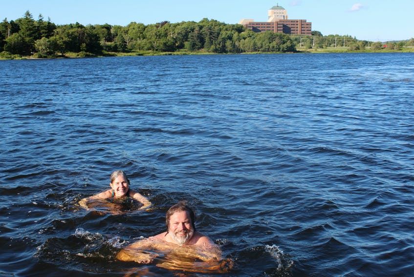 Jordan Young and Kathleen Parewick take an evening swim in Long Pond in St. John's, with the Confederation Building in the background.