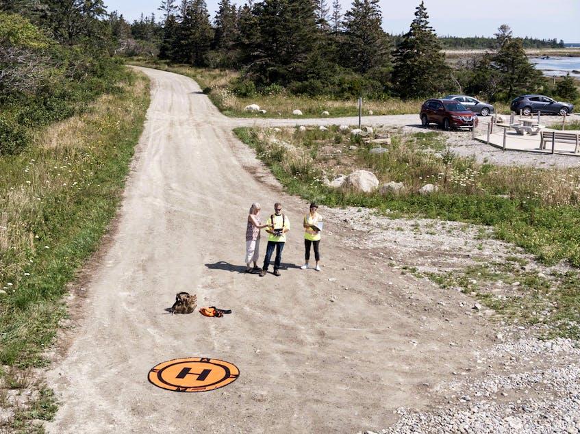 Reporter Carla Allen, drone pilot Steve St. Clair and visual observer Lesley Schwartz, through the