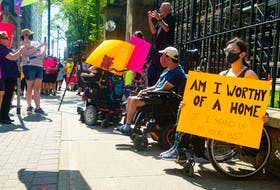 April Hubbard holds a sign as she attends a Disability Rights Coalition rally outside Province House on Friday, Aug. 13, 2021. Ryan Taplin - The Chronicle Herald