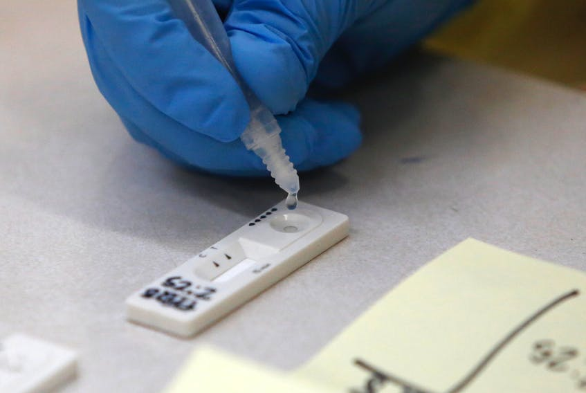 A sample from a patient swab is dropped on a test strip at a rapid testing site at Central Spryfield School in Halifax in May.