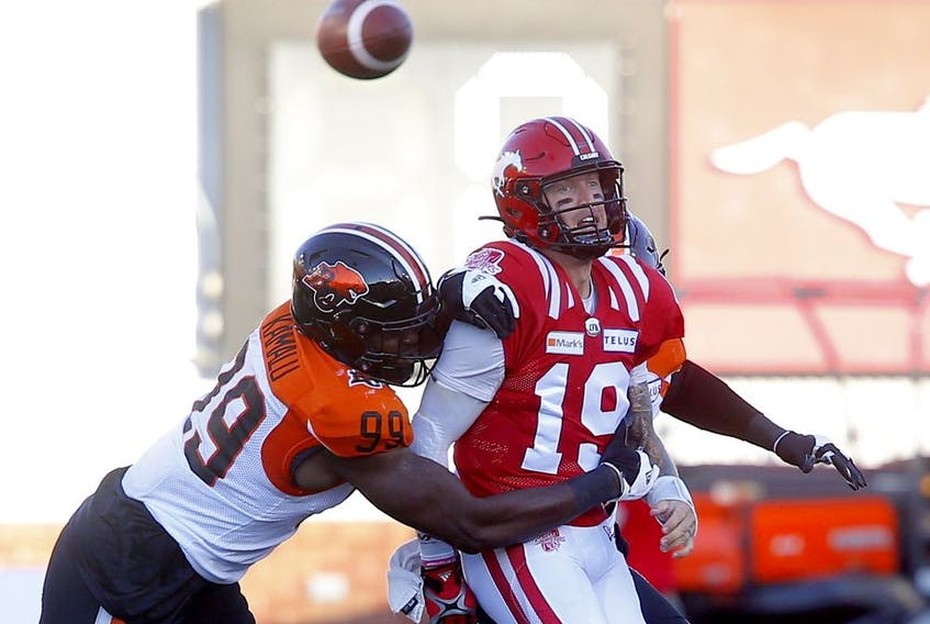 Calgary Stampeders quarterback Bo Levi Mitchell is harassed by the B.C. Lions' Ufomba Kamalu at McMahon Stadium in Calgary on Thursday, Aug. 12, 2021.