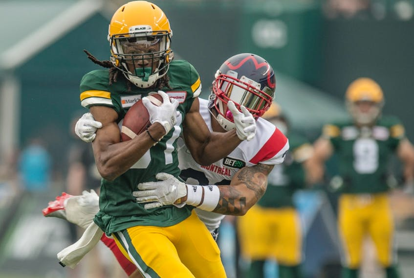 Derel Walker (87) of the Edmonton Elks is hauled down by Tre Watson (33) of the Montreal Alouettes at Commonwealth Stadium in Edmonton on Aug. 14, 2021.