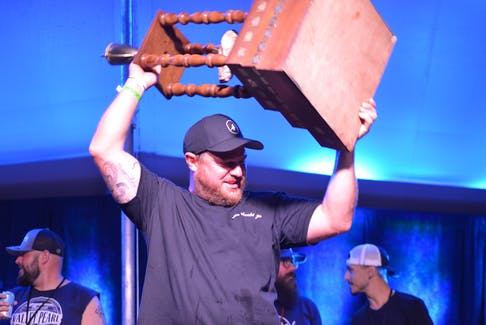 Eamon Clark hoists the Shuck Cup after being named the winner of the 2021 Canadian Oyster Shucking Competition. Clark is now a 10-time Canadian champion.