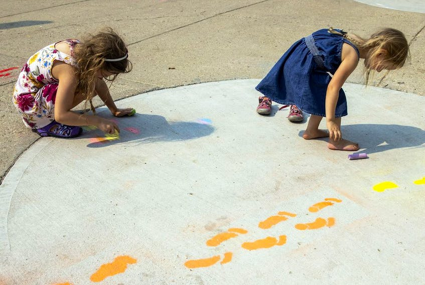Nine-year-old Elizabeth Prokop, left, and her four-year-old sister Evelyn use some chalk to make some footprints. Photo taken on Saturday, Aug. 14, 2021 in Regina. TROY FLEECE / Regina Leader-Post