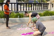 The Regina Downtown BID, Warehouse BID and the Regina Farmers' Market are hosting the collaborative Footprints Commemorative Indigenous Art Project, to commemorate the individuals found in unmarked graves on residential school sites in Saskatchewan. Indigenous artist Brandy Jones, left, looks on as José O'Blenis and her daughter Andy stencil her designs onto the sidewalk on Saturday, August 14, 2021 in Regina.