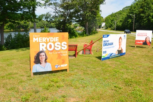 Lunenburg West election campaign signs stake out party territory on the grass next to the Veterans Memorial Bridge in Bridgewater.