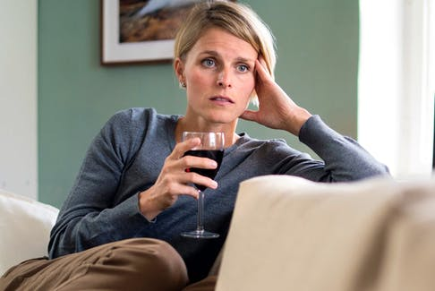 A woman with a glass of wine indoors at home.