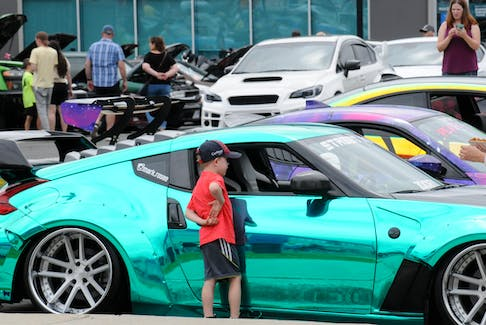 A young lad admires this brightly colored sports on display at the Wheels for Wishes auto show at Bristol Court on Saturday. -Joe Gibbons/The Telegram