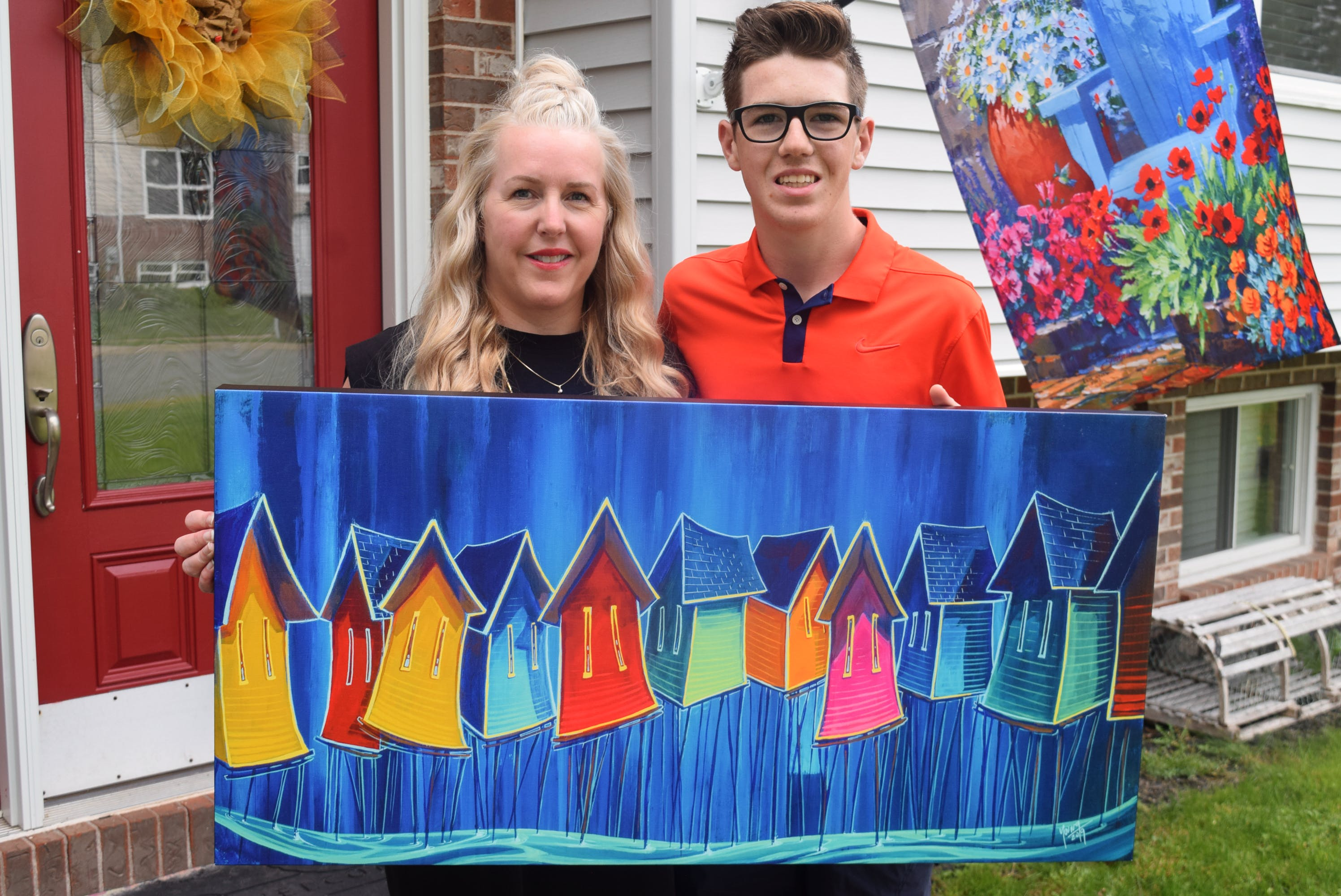 Jax Gaudet and his mother, Lana McMackin, hold up a painting by Adam Young of Young Studios that will be auctioned online for Jax's Make-A-Wish fundraiser. Before this, he has an even bigger fundraiser - VIP weekend passes for County Rocks the Hub and Rock the Hub festivals.
