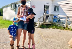 Alison Lewis, centre, with her children three-year-old Colten and seven-year-old Nora, stand outside of the voting station in Howie Centre at the Royal Canadian Legion branch 151.