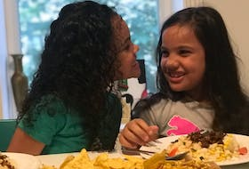Twins Jade and Delilah MacLeod enjoying mealtime at home.