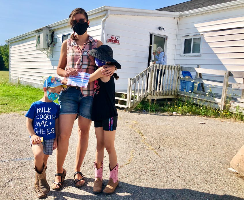 """Alison Lewis, centre, with her children three-year-old Colten and seven-year-old Nora, stand outside of the voting station in Howie Centre at the Royal Canadian Legion branch 151. """"I work in education so that's always on my mind,"""" Lewis said about important issues for her this election. """"Mental health is also important to me.""""  - Nicole Sullivan"""