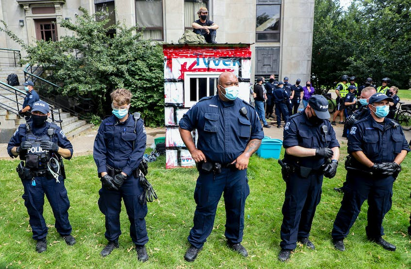  A lone protester atop a temporary shelter refused to budge for hours while being surrounded by Halifax police Wednesday, Aug. 18, 2021. He eventually came down on a ladder and was immediately arrested. - Tim Krochak