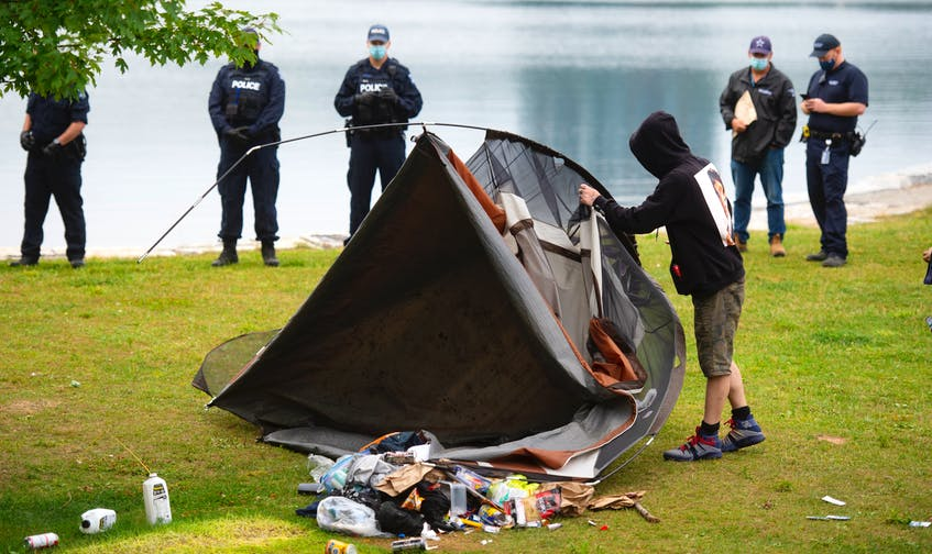 A homeless man is forced to dismantle his tent in Horseshoe Island Park in Halifax during a police sweep of encampments in public spaces on Aug. 18, 2021. - Ryan Taplin