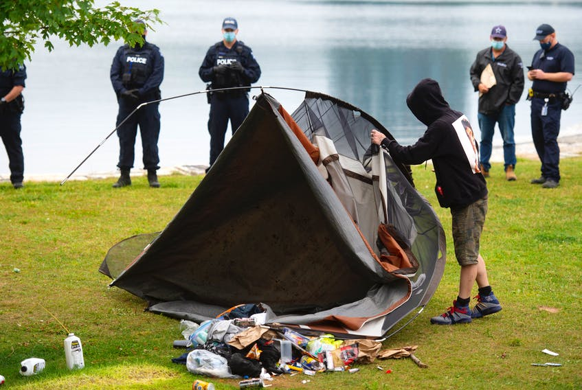 A homeless man is forced to dismantle his tent in Horshoe Island Park in Halifax during a police sweep of encampments in public spaces.