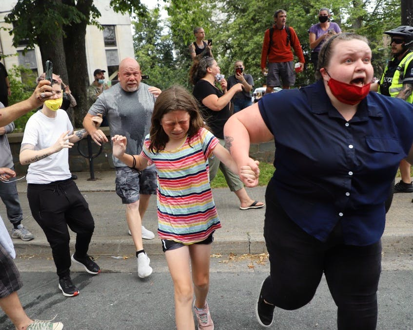 A child who was pepper sprayed by police is rushed away during a massive protest over the removal of temporary homeless shelters on Wednesday. - Tim  Krochak