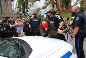 A woman arrested as protesters clashed with police in Halifax on Wednesday, Aug. 18, 2021, over a crackdown on temporary housing sites.