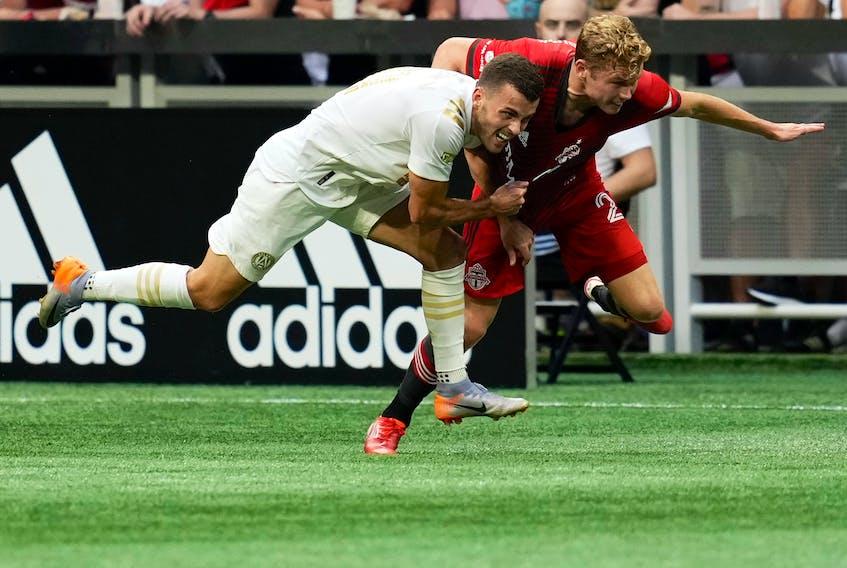 Atlanta United defender Brooks Lennon (left) battles with Toronto FC's Jacob Shaffelburg during the first half at Mercedes-Benz Stadium on Wednesday, Aug. 18, 2021.