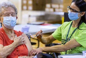 Shirley Banks, 88, flinches a bit in anticipation of getting her needle, wielded by public health nurse Stephanie McKee as the first COVID-19 vaccine was injected at the North London Optimist Centre on Cheapside Street in London, Ont.