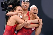 Canada's Penny Oleksiak (L), Margaret MacNeil (C) and Kayla Sanchez (R) celebrate as they take second place in the women's 4x100m freestyle relay swimming event.