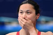Canada's Maggie Mac Neil reacts after taking gold in the final of the women's 100m butterfly swimming event.