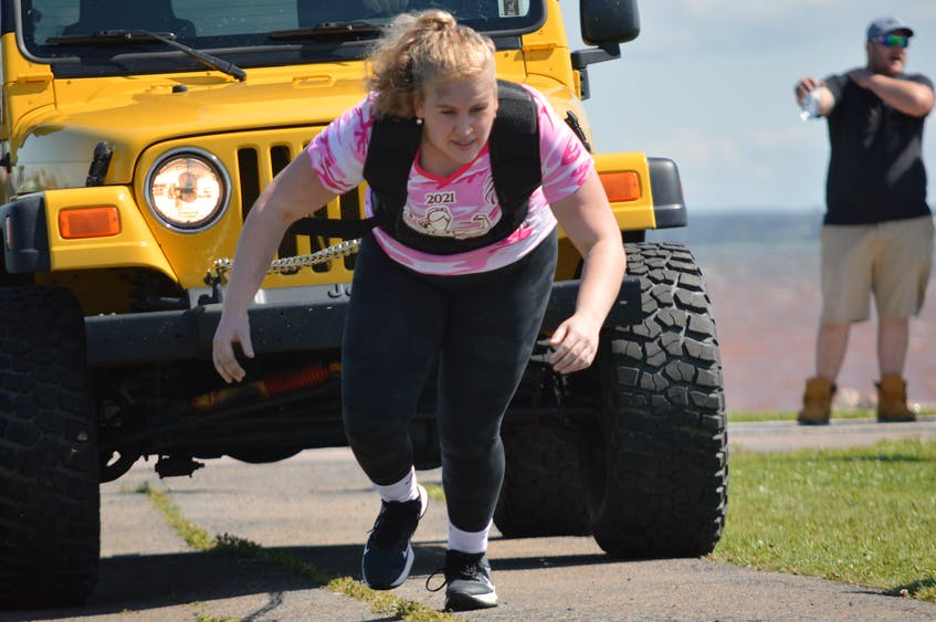 Elizabeth Burt pulls a Jeep behind her as part of a strongwoman show at Atlanticade Saturday afternoon. - Kyle Reid
