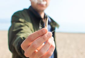 Young man holding a lit marijuana joint while smoking on the beach. Blur background and copy space right.