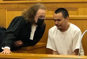 Accused murderer Patrick Sulurayok (right), 30, speaks with his defence lawyer, Bob Buckingham, in Newfoundland and Labrador Supreme Court in St. John's Aug. 2. Sulurayok is charged with second-degree murder in the death of Bernard Otuk at a rental cabin on Roaches Line on June 22.
