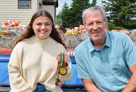 Eighteen-year-old Hannah shows off the gold medal her father Michael, right, won in rowing at the 1992 Barcelona Olympic Games. DAVID JALA/CAPE BRETON POST