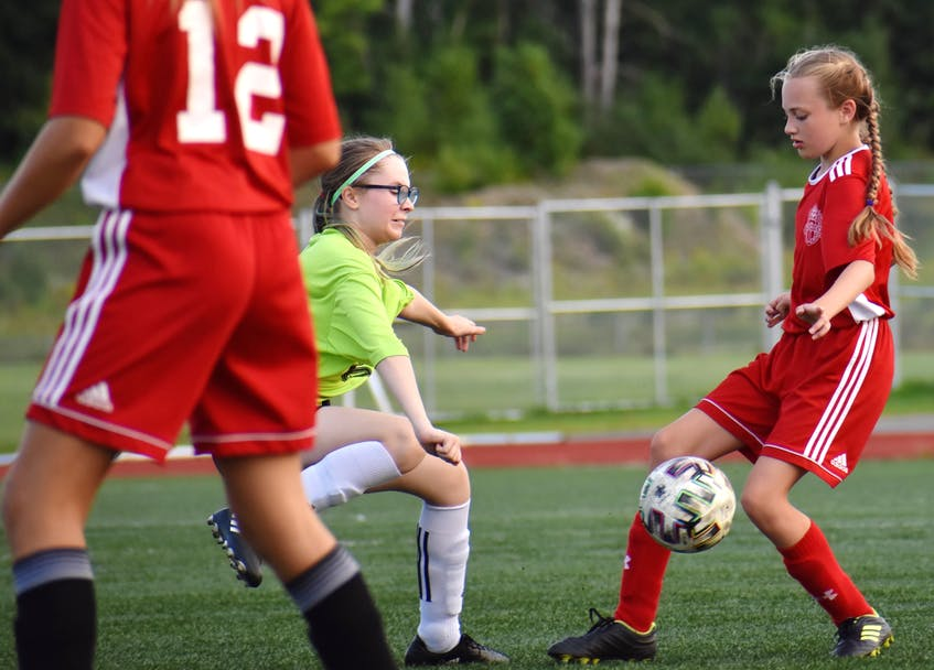 Carly MacLean of Riverview, right, controls the ball as she's pressured by a New Waterford Wolves player during Cape Breton and District Soccer League under-13 girls' quarterfinal action at Cape Breton Health Recreation Complex on Friday. Riverview won the game 4-0. JEREMY FRASER/CAPE BRETON POST. - Jeremy  Fraser