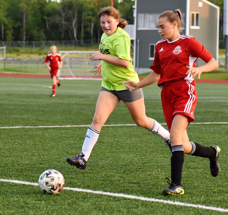 Vada Kennedy of Riverview, right, works her way to the net as she's chased by Madison McIsaac of New Waterford during Cape Breton and District Soccer League under-13 girls' quarterfinal action at Cape Breton Health Recreation Complex on Friday. Riverview won the game 4-0. JEREMY FRASER/CAPE BRETON POST. - Jeremy  Fraser