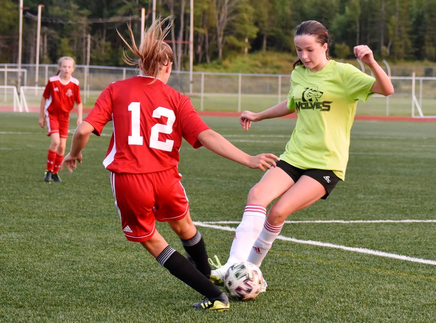 Taylor Stubbert of New Waterford, right, picks up the ball and she's pressured by Vada Kennedy during Cape Breton and District Soccer League under-13 girls' quarterfinal action at Cape Breton Health Recreation Complex on Friday. Riverview won the game 4-0. JEREMY FRASER/CAPE BRETON POST. - Jeremy  Fraser